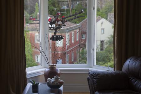 リビング ルームの窓の外で浮かぶカメラとドローン