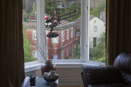 spy camera: A drone with a camera hovering outside living-room window Stock Photo