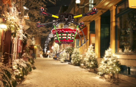 A flying quadrocopter delivering a basket of Christmas goodies above covered with snow beautifully decorated street