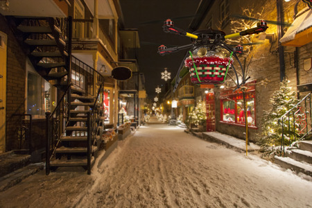 street lamp: A flying quadrocopter delivering a basket of Christmas goodies above covered with snow beautifully decorated street