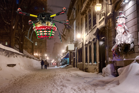 A flying quadrocopter delivering a basket of Christmas goodies above covered with snow beautifully decorated street photo