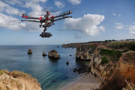 Een drone met verhoogde landingsgestellen en een camera vliegen in prachtige wolkenluchten langs spectaculaire kliffen met een kalme zee op de achtergrond Stockfoto