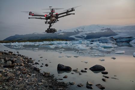 Eine Drohne mit erhobenen Fahrwerke und eine Kamera fliegt über Eisberge mit einem Gletscher im Hintergrund