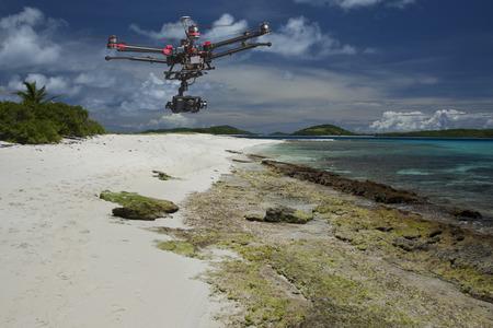 Ein fliegender Hubschrauber mit erhobenen Fahrwerke und eine Kamera fliegt über weiße Sende einer schönen tropischen Insel mit dramatischen Himmel im Hintergrund