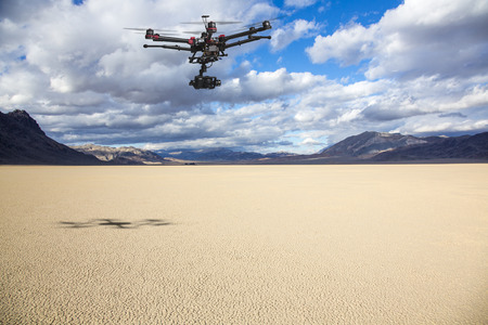 A flying helicopter with raised landing gears and a camera flying over mesmerizing view of Racetrack Playa Standard-Bild