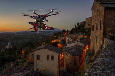 A drone making delivery of a bouquet of red roses above empty streets of old city
