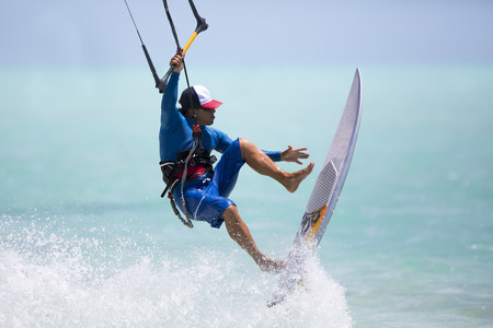 A kitesurfer performing an aerial trick riding strapless surfboard on a sunny day. Stock Photo