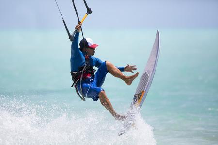 Ein Kitesurfer Durchführung einer Luft Voltigieren trägerlosen Surfbrett an einem sonnigen Tag.
