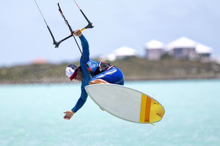 kite: A kitesurfer performing an aerial trick riding strapless surfboard on a sunny day. Stock Photo