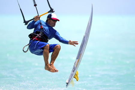 strapless: A kitesurfer performing an aerial trick riding strapless surfboard on a sunny day. Stock Photo