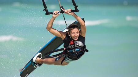 A smiling girl performing a relay jump on a kiteboard. The subject is surrounded with drops of water and tropical sea in the background.