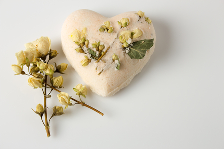 Bath bombs decorated with dried linden flowers on a white background Stock Photo