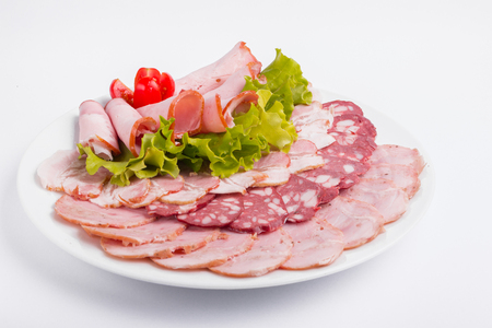 Food tray with delicious salami, pieces of sliced ham, sausage, tomatoes, salad