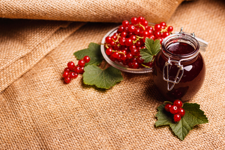 fresh red currant and jam on the rustic background. Stock Photo
