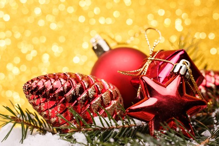 pinecones: Christmas composition of Christmas tree toys on a gold background. Stock Photo