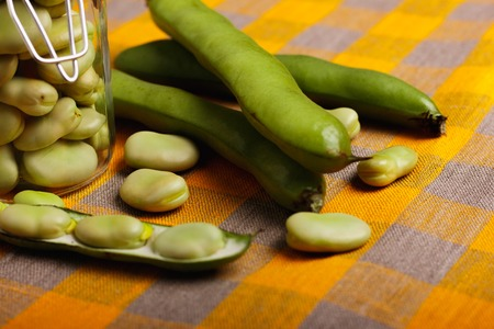 fresh broad beans on a rustic background.