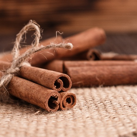 Cinnamon essential oil on a wooden background.