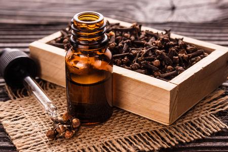 Aceite esencial de clavo sobre un fondo rústico de madera.