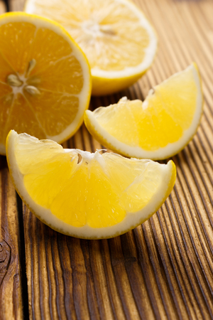 Lemon and juice on a wooden background.