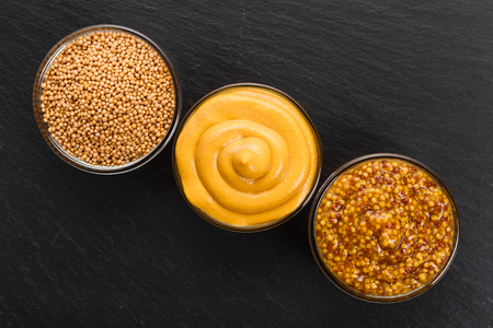 Set of different species of mustard on a rustic background.