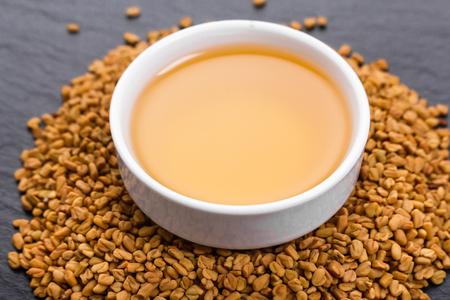 fragrant grains of fenugreek on a rustic background.