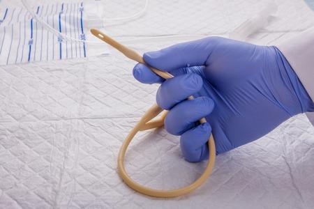 Nurse inflates urinary catheter bulb with leg drainage bag on sterile field