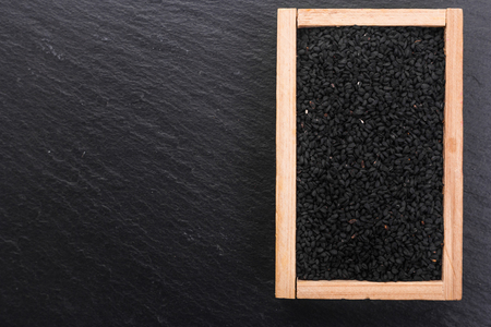 grains of black cumin and oil on the rustic background. Stock Photo