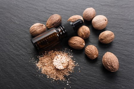 nutmeg essential oil on a dark stone background.