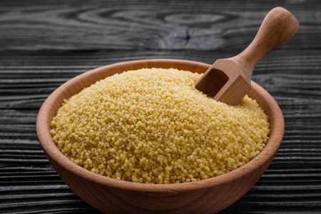 fresh couscous on a wooden rustic background.
