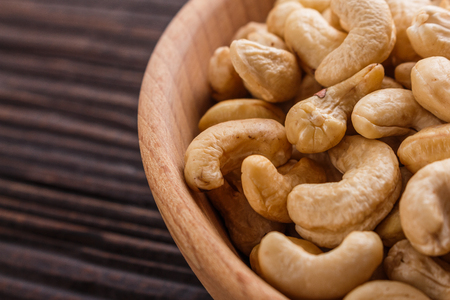 cashew nuts on a rustic wooden background.