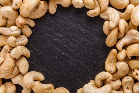 cashew nuts on a dark stone background.