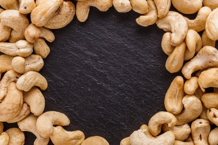 cashew nuts on a dark stone background.