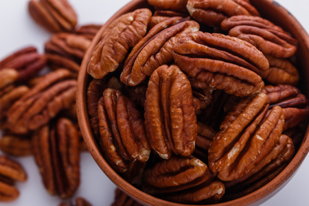 delicious pecan nuts on a white acrylic background.