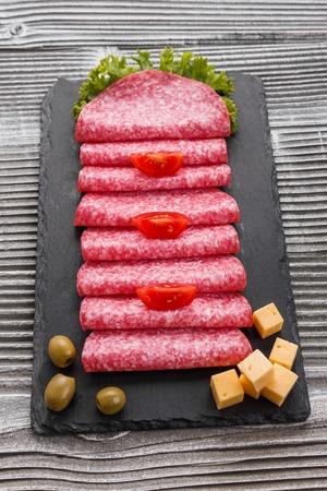 delicioso salami en rodajas en un plato de piedra. Foto de archivo