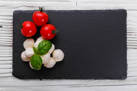 Mozzarella tomatoes and basil on a wooden rustic background.