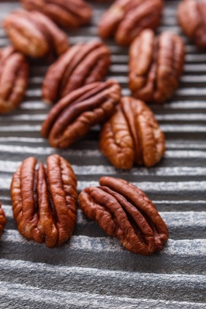 delicious pecan nuts on a rustic wooden background.