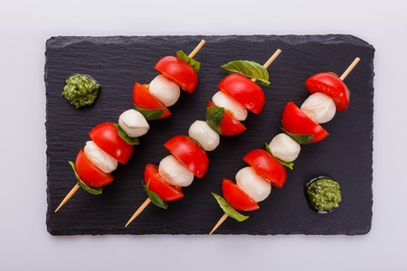 Caprese salad on a white acrylic background.