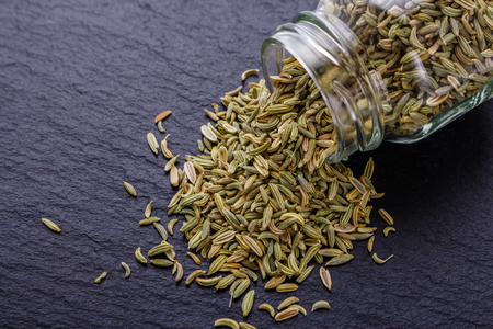 Essential oil of fennel seeds on a dark stone background. 免版税图像