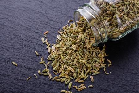 Essential oil of fennel seeds on a dark stone background. Stok Fotoğraf - 110185434