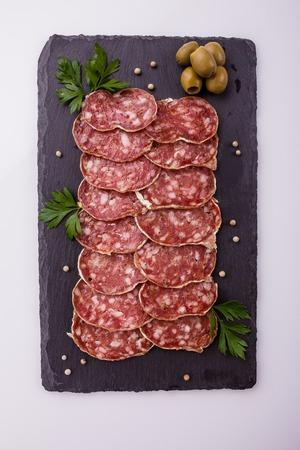 Saucisson sec delicious french salami on a white background. Фото со стока