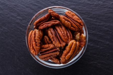 delicious pecan nuts on a dark stone background. Stockfoto