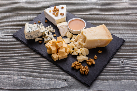 set of different cheeses on a wooden rustic background. Reklamní fotografie