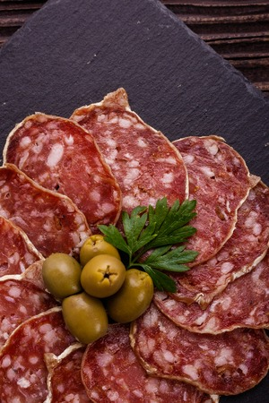Saucisson sec delicious french salami on a wooden background.