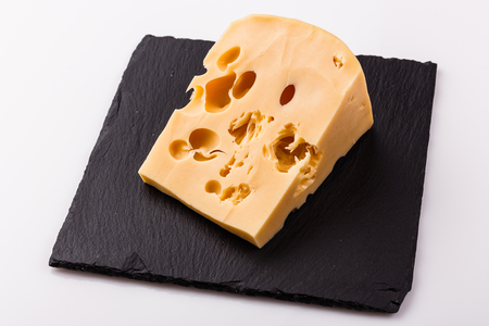 Piece and slices of cheese on a white background.