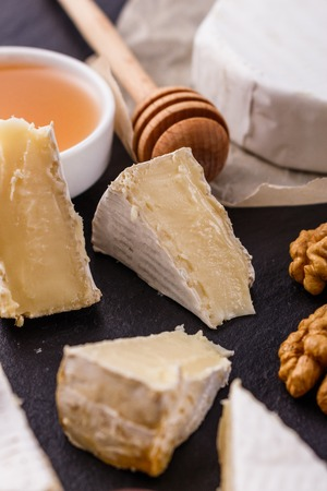 delicious creamy camembert cheese on a wooden rustic background.