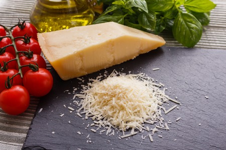 fragrant grated Parmesan on a slate stone slicing board. Standard-Bild