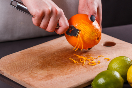 young woman in a gray aprons, cuts an orange zest.
