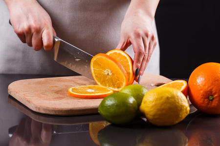 young woman in a gray aprons cuts an orange.