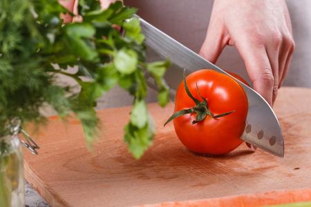 young woman slicing a tomato in a gray apron. Banco de Imagens