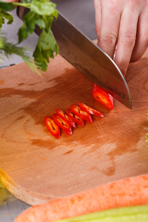 young woman slicing peppers in a gray apron. Banco de Imagens